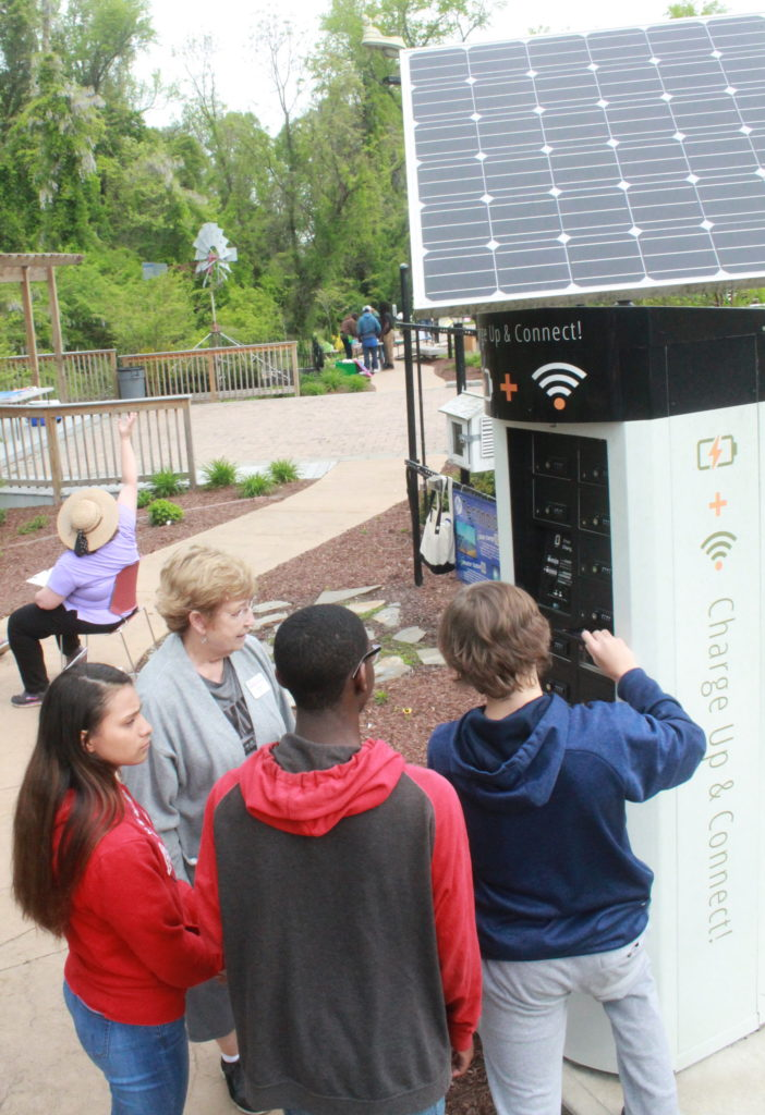 students look at an outdoor, solar-powered charging station for devices