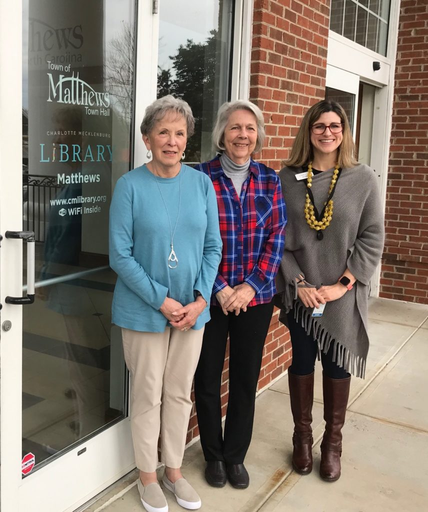 three women standing outside the door to the Matthews library